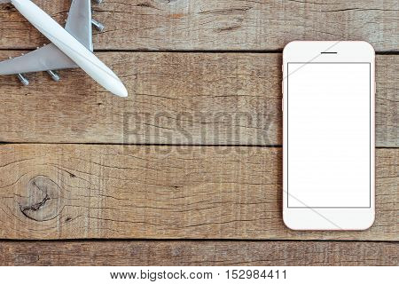 phone and airplane toy on wood table transport business concept top view mock up phone blank screen
