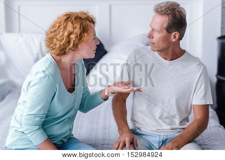You are wrong. Irritated senior couple sitting on the bed while arguing at home