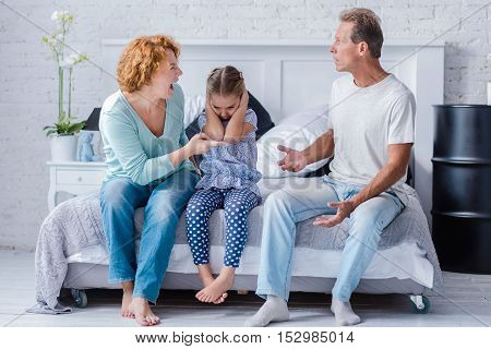 Listen to me now. Hateful wife shouting on her husband while sitting on the bed near their granddaughter