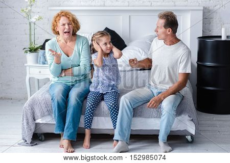 I hate my grandparents quarreling. Furious grandfather going to hit his wife while sitting on the bed and arguing near their granddaughter