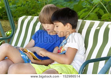 Two Boys Sitting in a Swing Looking at a Catalogue