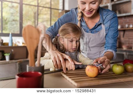 Little mothers helper. Joyful cheerful involved girl cutting apples with her mother while sitting at the table and cooking in the kitchen
