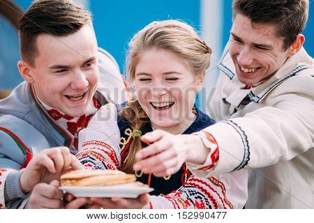 Gomel, Belarus - March 12, 2016: Happy young people dressed in national folk clothes posing with a plate of pancakes in hands at traditional folk Celebration of Maslenitsa Shrovetide holiday
