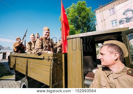 Gomel, Belarus  - May 9, 2016: Group Of Men Sitting In Russian Soviet Military Truck ZIS-5V In Soldiers Uniform With Weapon Of WW2 Time And Victory Red Flag. Preparing For The 9th May Victory Parade