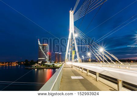 Riga, Latvia - July 01, 2016: Close View Of Vansu Cable-Stayed Bridge In Bright Night Illumination Over The Daugava River, Skyscrapers Of Downtown And Blue Sky Backgroung
