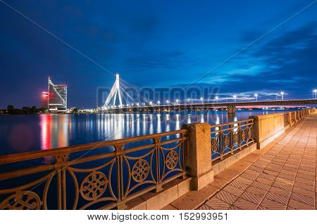 Riga, Latvia. View Of Famous Vansu Cable-Stayed Bridge In Bright Night Illumination From Deserted Embankment Of The Daugava Or Western Dvina River Under Dramatic Blue Summer Sky.