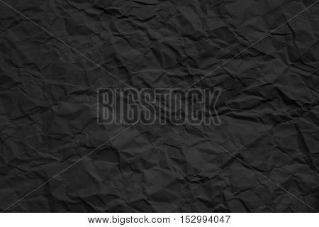 Texture of crumpled dark paper. Closeup photo.