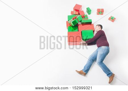 Black Friday 2016 at United States. Funny father holding many gift boxes for kids and running. Copy space at white background. Big gift box Cristmas shopping. Xmas, New Year holiday Merry Christmas