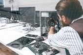 Electronic repairman working with CPU, double exposure. Unrecognizable engineer disassembling computer unit in repair shop poster