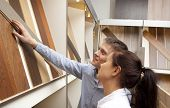 Couple looking at parquet board for home flooring in store, in home improvement warehouse exterior poster