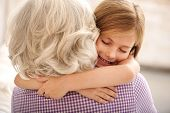 I love you. Affectionate granddaughter and grandmother are hugging. Girl is smiling with closed eyes poster