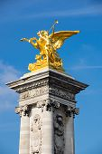 """Gilded """"Fames"""" sculptures on the socle counterweights of Pont Alexandre III over the river Seine in Paris France poster"""