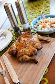Whole cooked chicken on cutting board served with salad poster