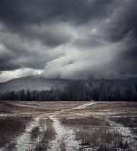 Dark Gloomy Landscape with Country Road in Snow. Moody Sky Background with Epic Dramatic Clouds around Mountains. Cold Winter Fantasy Scenery. Toned HDR Styled Photo. poster
