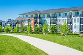 Concrete pathway across green lawn in front of residential condo building. Residential apartment building on sunny day with blue sky. poster
