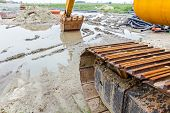 View under the arm of excavator. Reflection on water surface construction site after rain poster