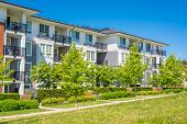 Brand new condo building on sunny day in British Columbia Canada. Luxury apartment building with green lawn in front poster