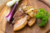 Fried streak of lean (fatback) served with fried and fresh young onion on wooden cutting board poster