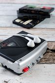 Old casette tape player and recorder with earphones on wooden background poster