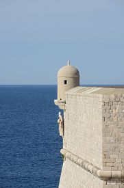 Stone wall and tower with St. Blaise statue overlooking sea Croatia Dubrovnik.