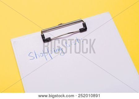 List Of Paper With Words Shopping List On Yellow Background. Copy Space. Flatlay.