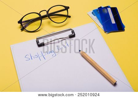 List Of Paper With Words Shopping List, Credit Cards, Pen On Yellow Background. Copy Space.