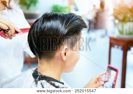 Beauty, hairstyle, treatment, hair care concept, young woman and hairdresser cutting hair at hairdressing salon. Hairdresser cuts happy girl's hair. Hairstylist serving client at barber shop poster