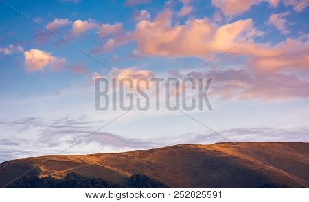 Reddish Cloudscape Over The Mountain Top. Beautiful Nature Background At Sunset