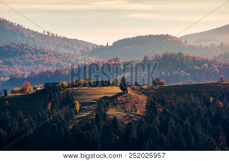 Village On Forested Rolling Hill In Haze. Beautiful Countryside Scenery In Mountain Of Romania At Su