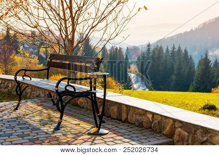 Bench On A Hill In Beautiful Autumn Countryside. Lovely Mountainous Landscape With Road Through Fore