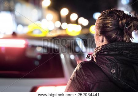 Taxis In The City Street At Night. Woman Looking For A Cab Ride. Back View Of Young Lady And Row Of