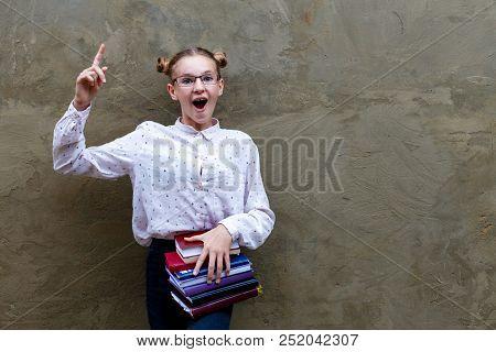 Little Genius Has An Idea. Happy Girl Keep Fingers Raised On Gray Background. Back To School. Little