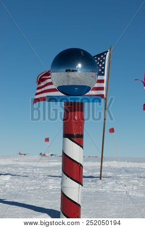 The South Pole Marker With The American Flag Behind It. The Marker Is Located At The South Pole Stat