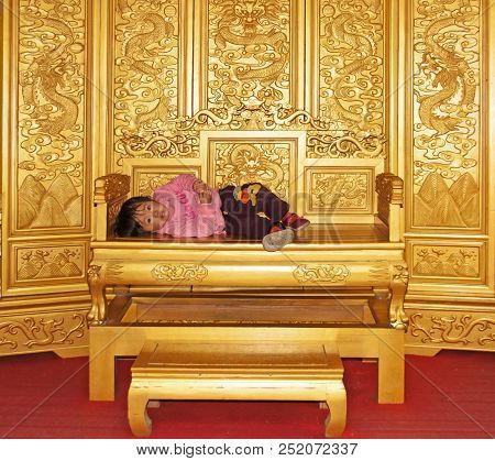 Beijing, China - October 29, 2011: A Little Girl Is Lying Bored On A Golden Emperor Throne Seat. Due