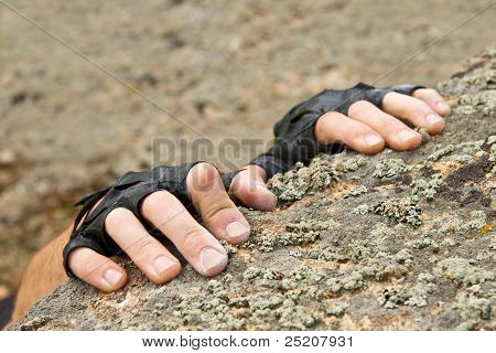 Two Hands Of Rock-climber Hanging On Stone