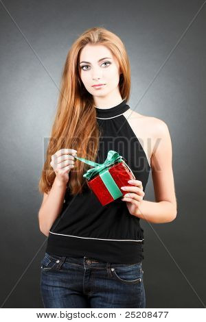 beautiful young girl with a gift in hand on a black background