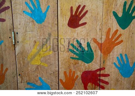 Red, Green, Blue, Orange And Yellow Hand Prints On A Fence