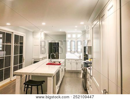 Modern interior design of white kitchen cabinets and cream quartz countertop, interior design of the kitchen, granite countertops, island of modern kitchen