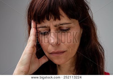 Worried Woman With Her Hand To Her Head