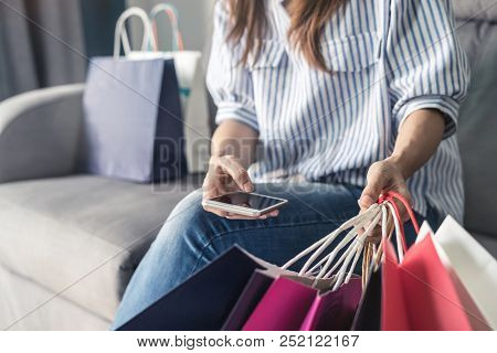 Happy Asian Woman Sitting On Sofa And Holding Credit Card And Smart Phone For Shopping Online Paymen