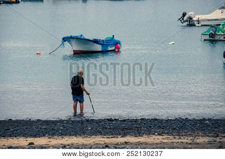 Old Man With Walking Stick, Soak His Feet On Coast Of Sea Near Boats In Port.