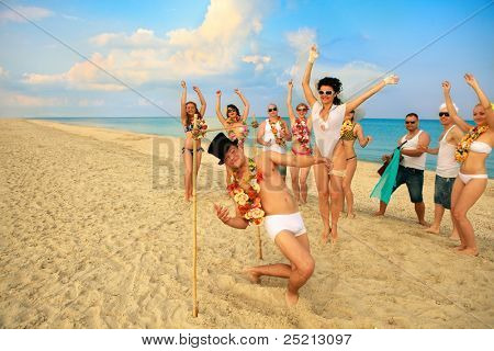 Beach wedding of happy newlywed couple have fun doing the limbo