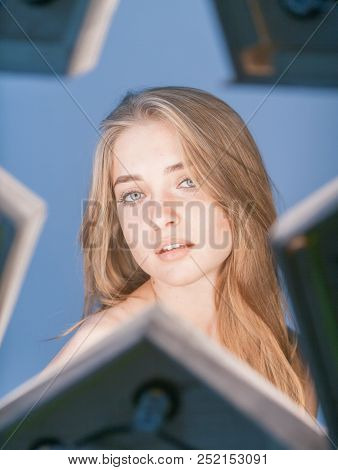Beautiful Young Longhaired Woman With Star Reflex In Eyes And Opened Shoulders On Blue Background