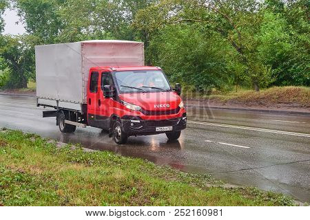 Krasnoyarsk, Russia - July 30, 2018: Iveco Daily Red Color Passing On The Wet Road To A Rain .