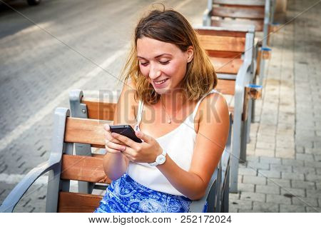 A Sexy Russian Blond Caucasian Girl Is Happy Getting Great News On Her Phone.