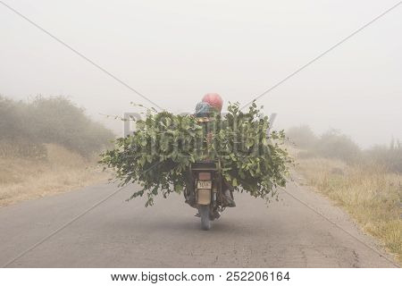 Daylaman, Iran - July 27, 2018 Mountain Side Road, Motorcycle Driving With Cut Branches Through Fogy