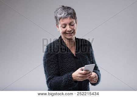 Attractive Senior Woman Typing On Her Mobile