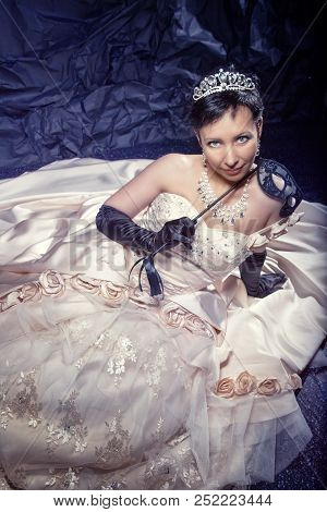brunette girl with short hair in crown with rhinestones and choker in ballroom, wedding dress with black satin gloves and black cloak with masquerade lace mask for new year on black uneven background poster