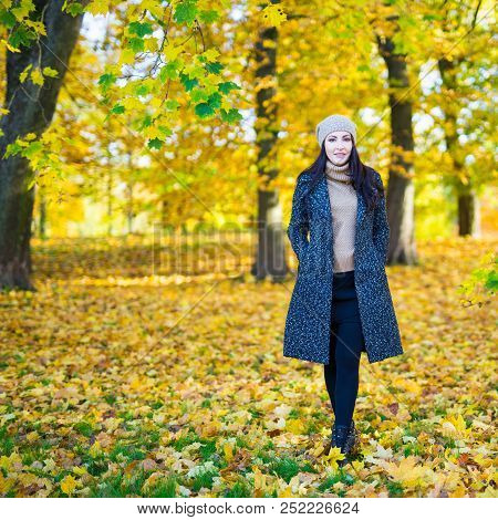 Full Length Portrait Of Young Beautiful Woman In Autumn Park