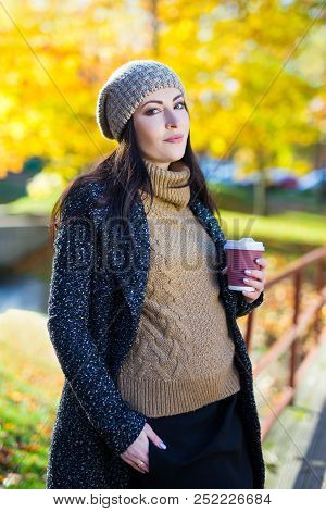 Young Beautiful Woman With Cup Of Coffee In Autumn Park